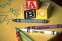 ABC blocks and crayons on notepad