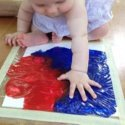 Baby pressing on bag with red and blue paint inside