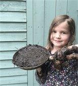 girl holding pan of mud