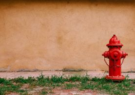 Red fire hydrant next to sidewalk