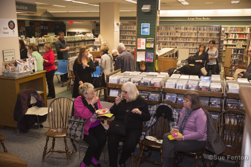Patrons attending a wine and cheese social at the public library