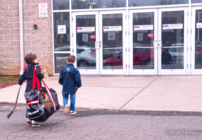 Children entering main entrance at Newington area with hockey equipment in hand