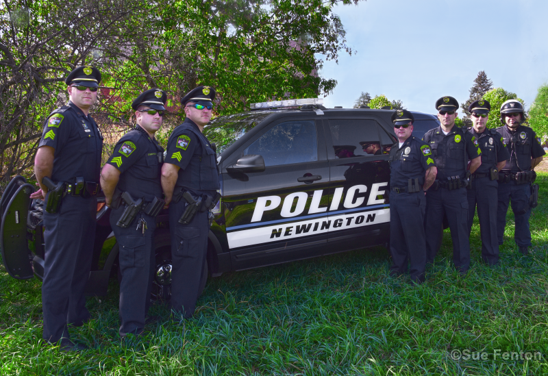 Seven members of the Newington Police Department posing for photo in front of fleet vehicle